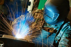 welder working with electrode at semi-automatic arc welding in m